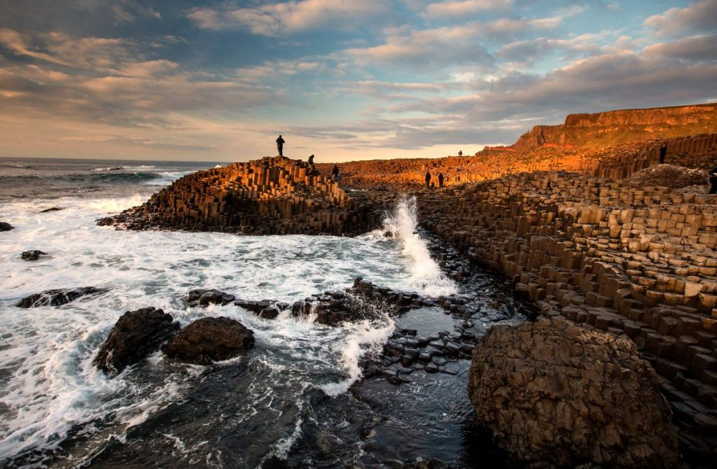 The Giants Causeway Official Guide image of the causeway at sunset looking north west towards rathlin island and scotland. The stones are in aan orange hue